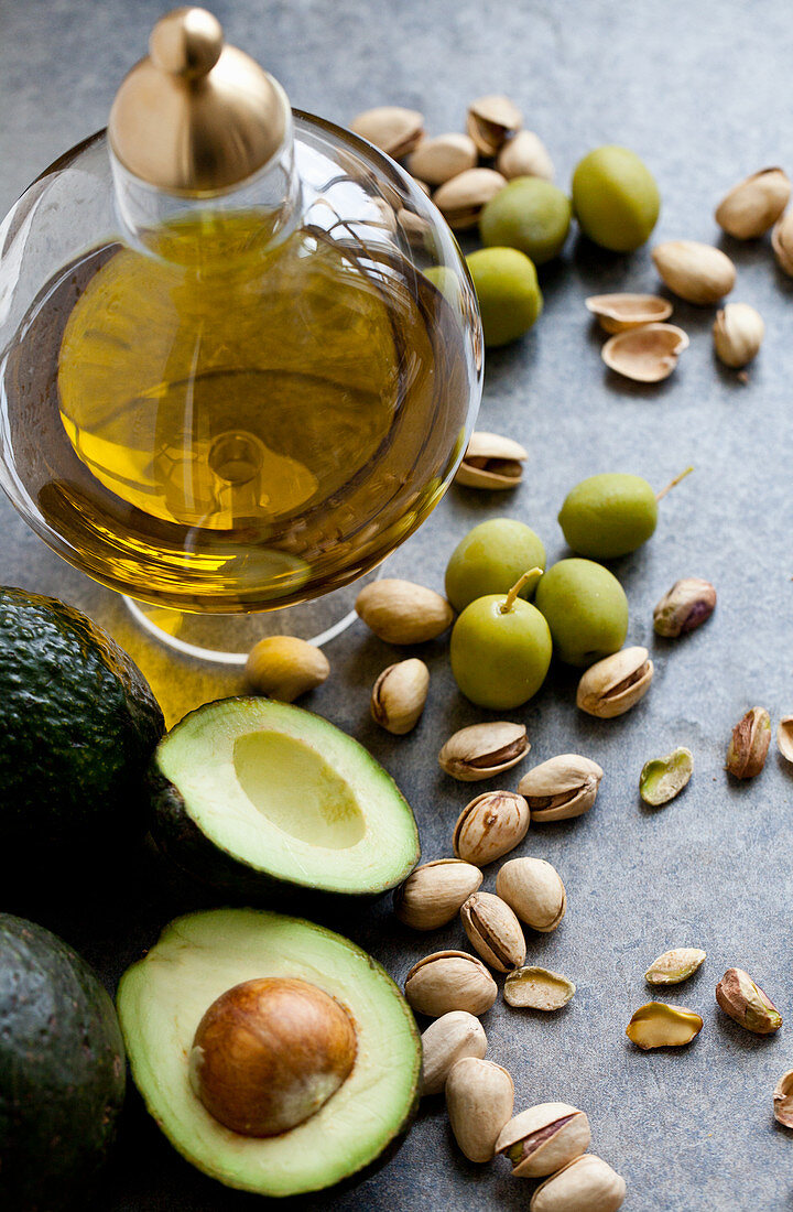 Healthy fats - a jar of olive oil, with olives, pistachio nuts and avocados sitting beside