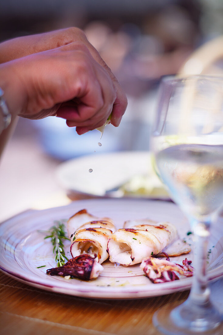 Dinner table woman squeezing lemon on a plate of grilled octopus