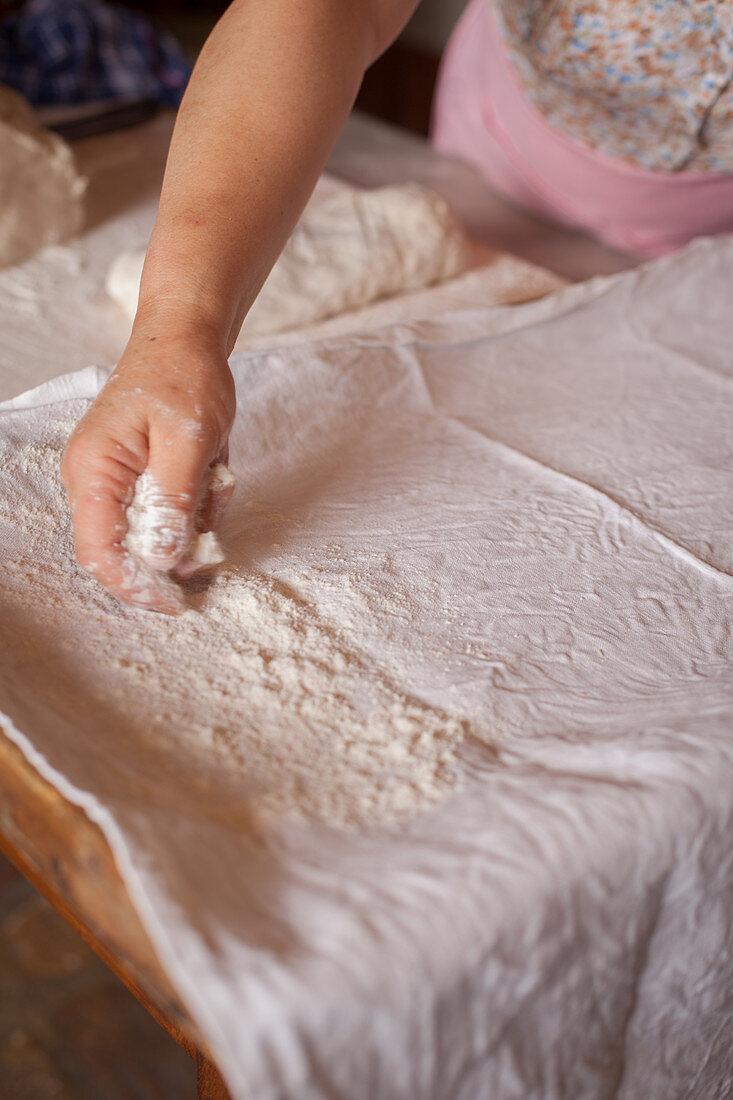 Baking bread (spreading flour on a cloth)