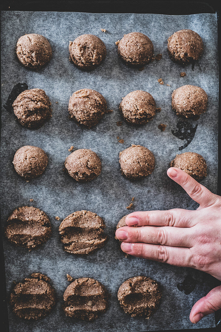 Flattening dough balls for chocolate cookies by hand