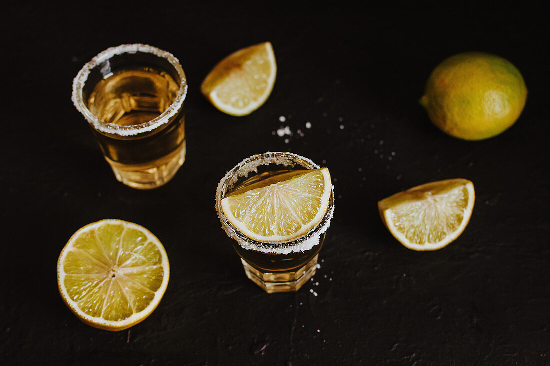 Two traditional tequila shots served with pieces of fresh lime and salt