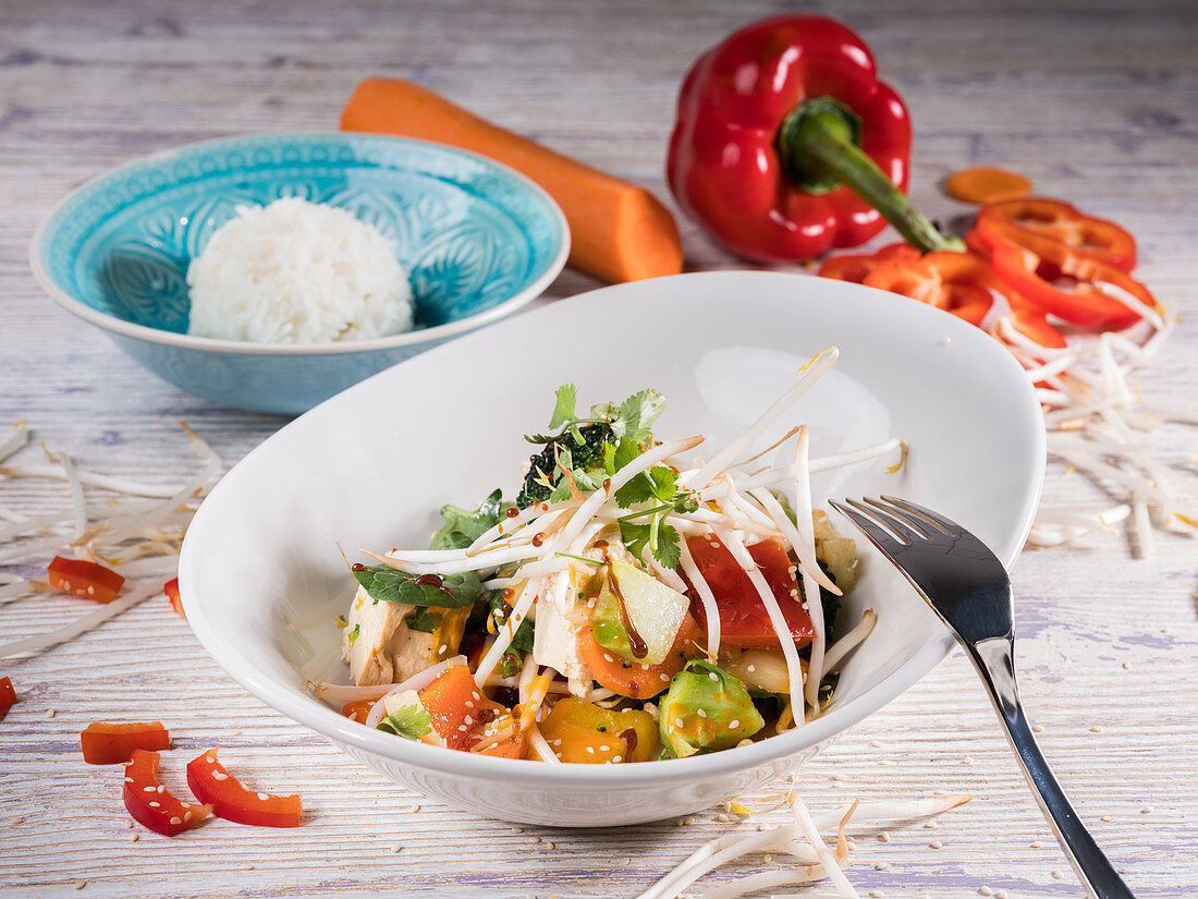 Asian salad with chicken breast, bean sprouts, rice, paprika, carrots and chervil