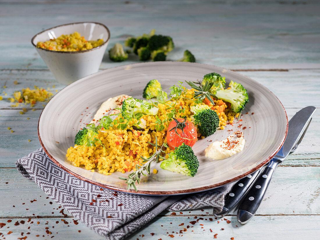 Oriental vegetable and bulgar wheat with broccoli, cherry tomatoes, chervil and rosemary