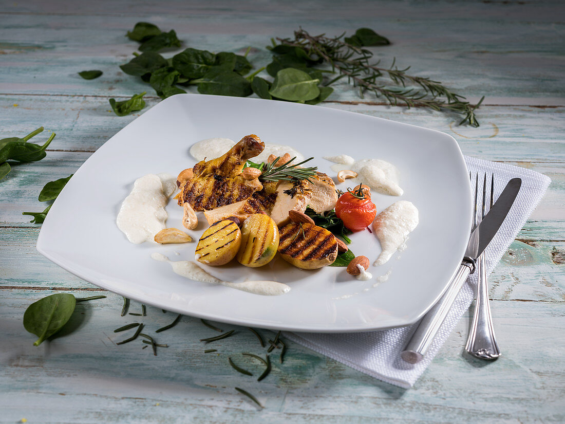 Chicken breast with grilled potatoes, cherry tomatoes, rosemary, spinach and almonds