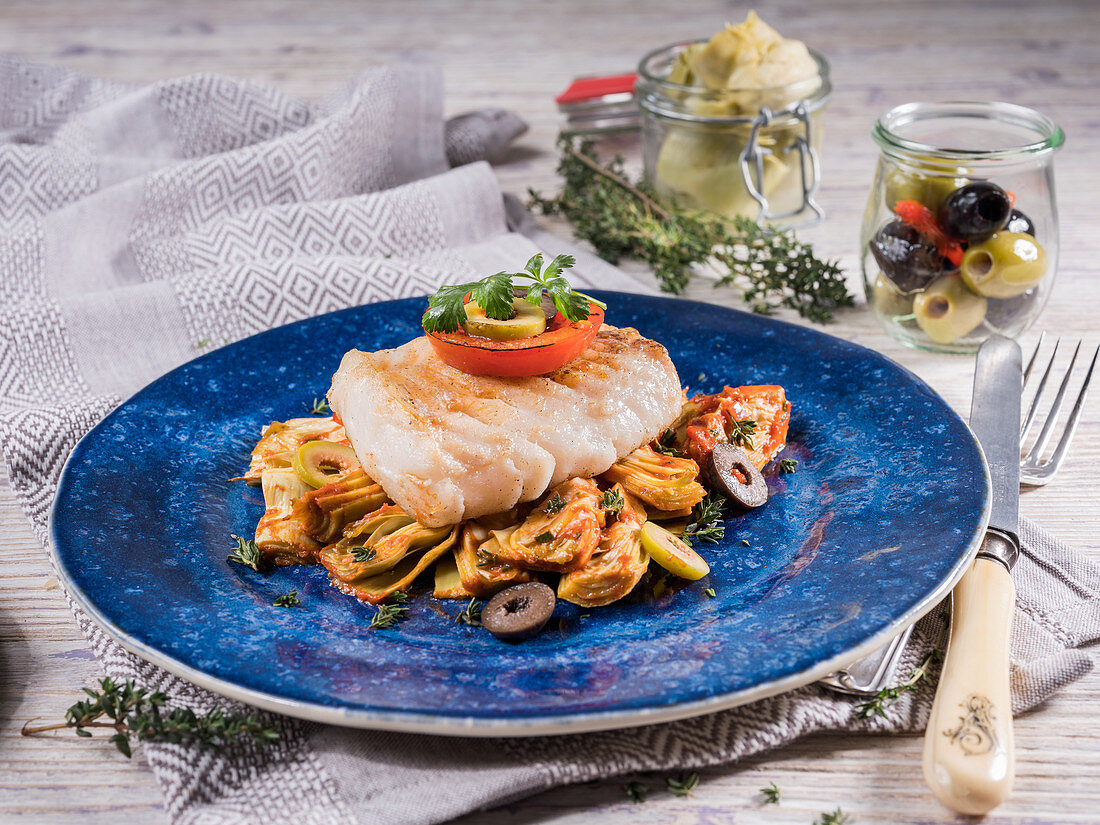 Fried halibut with artichokes, olives, chervil, thyme and tomato