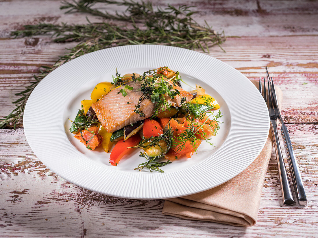 Fried salmon steak with vegetables and herbs