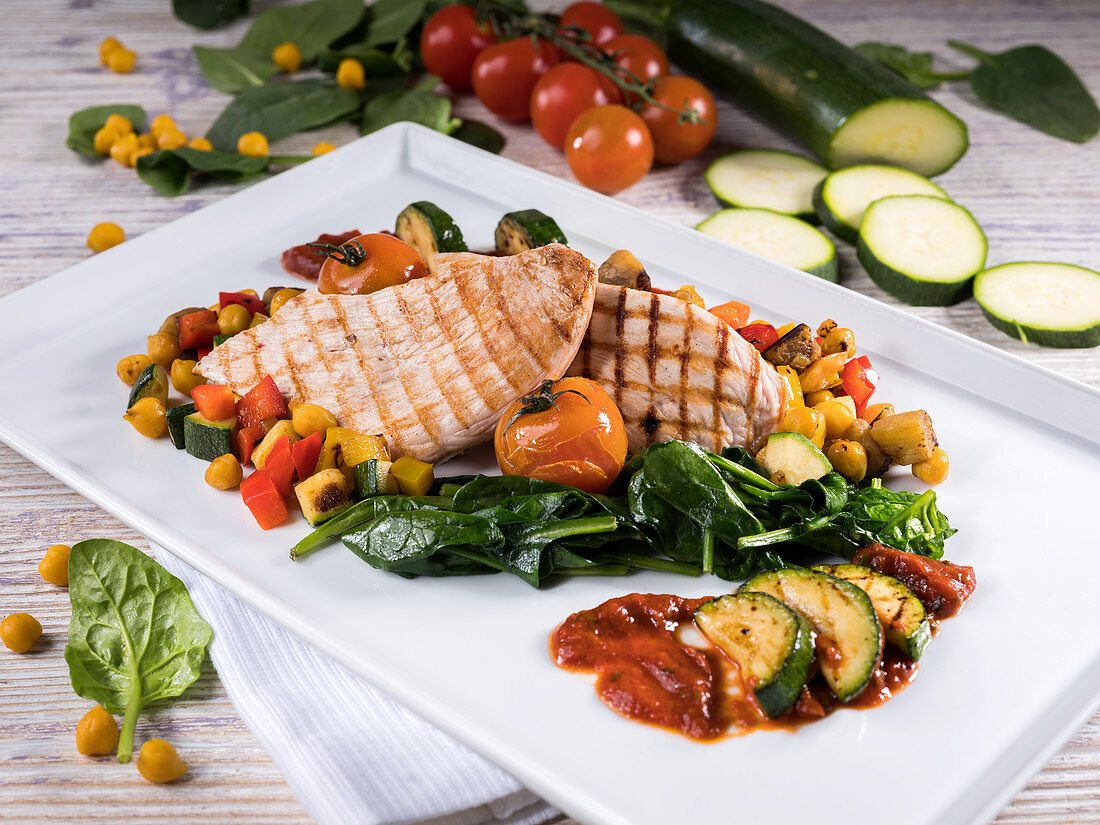 Grilled turkey steaks with spinach, zucchini, cherry tomatoes and chickpeas