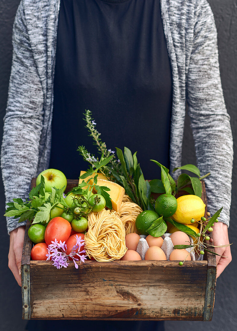 A woman holding a wooden crate of fruit, vegetables and other foodstuffs