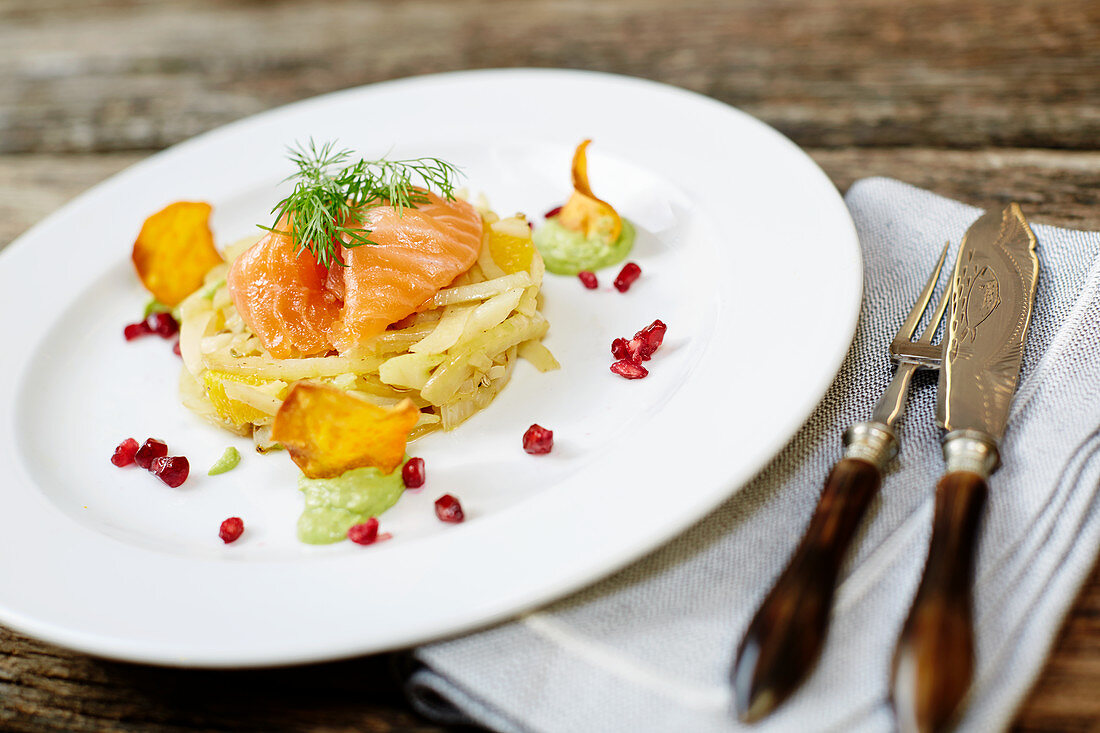 Smoked salmon on fennel with oranges, pomegranate seeds, potato chips and dill