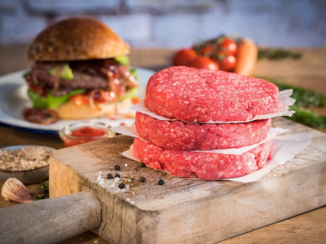 Raw hamburger patties, hamburgers, vegetables and spices