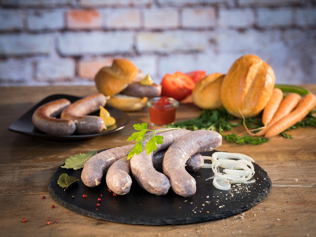 Fresh beef bratwurst in natural gut casing, with vegetables, bread and mustard