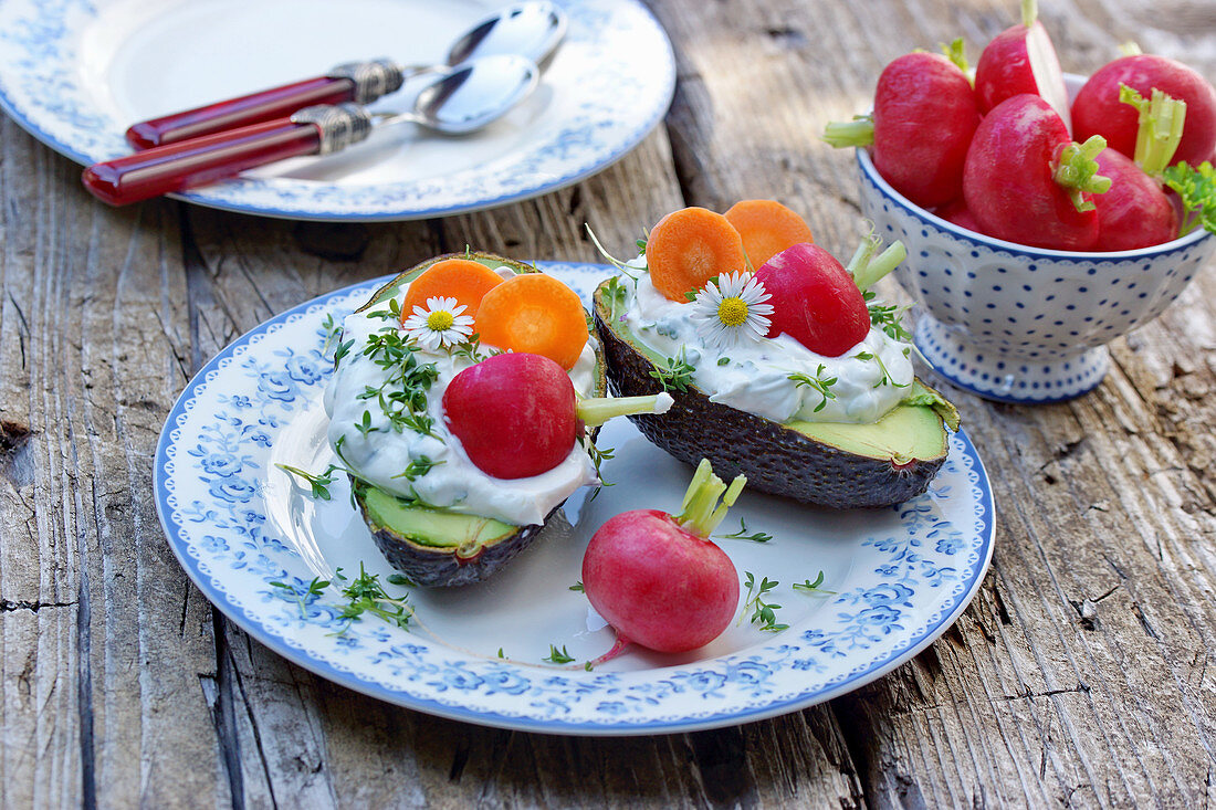 Avocados with herb quark, radishes, carrot slices, cress and daisies