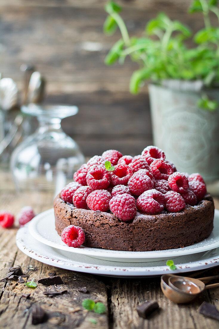 Chocolate cake with raspberries and powdered sugar