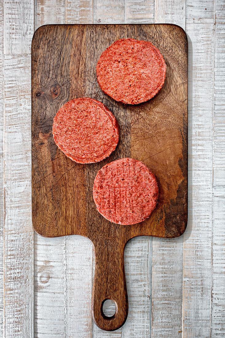 Raw hamburger patties on a wooden cutting board