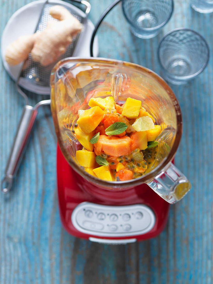 Ingredients for a smoothie (mango, papaya, passion fruit) in a blender