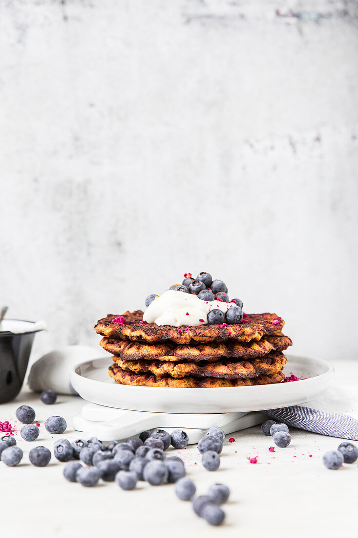 A stack of pumpkin waffle with blueberries and yoghurt