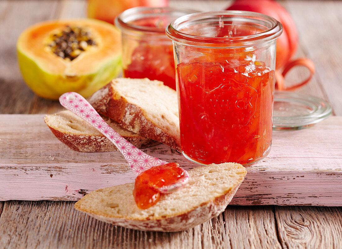 Papaya and nectarine jam in a mason jar on a wooden background