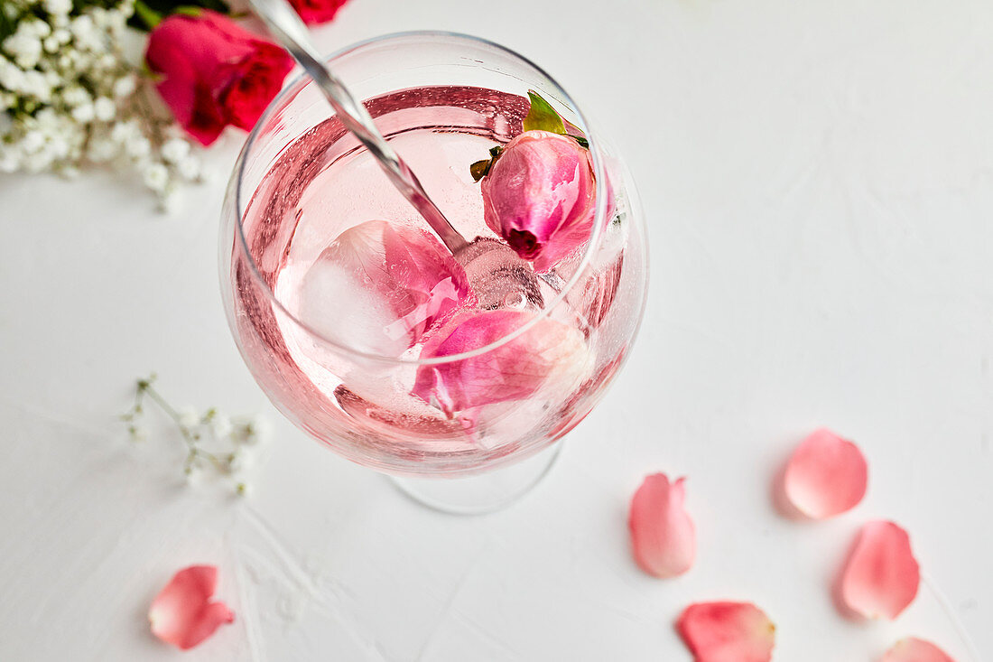 Stirring the gin and tonic cocktail with rose infused tonic