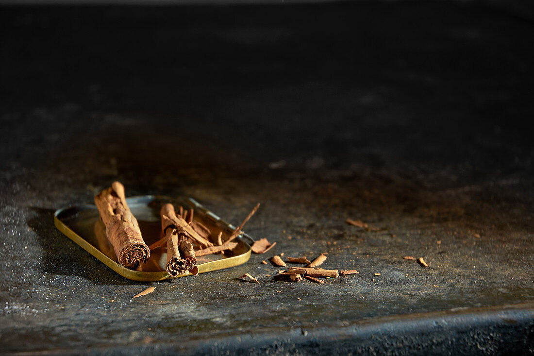 Cinnamon sticks on a tin lid on a black metal tray
