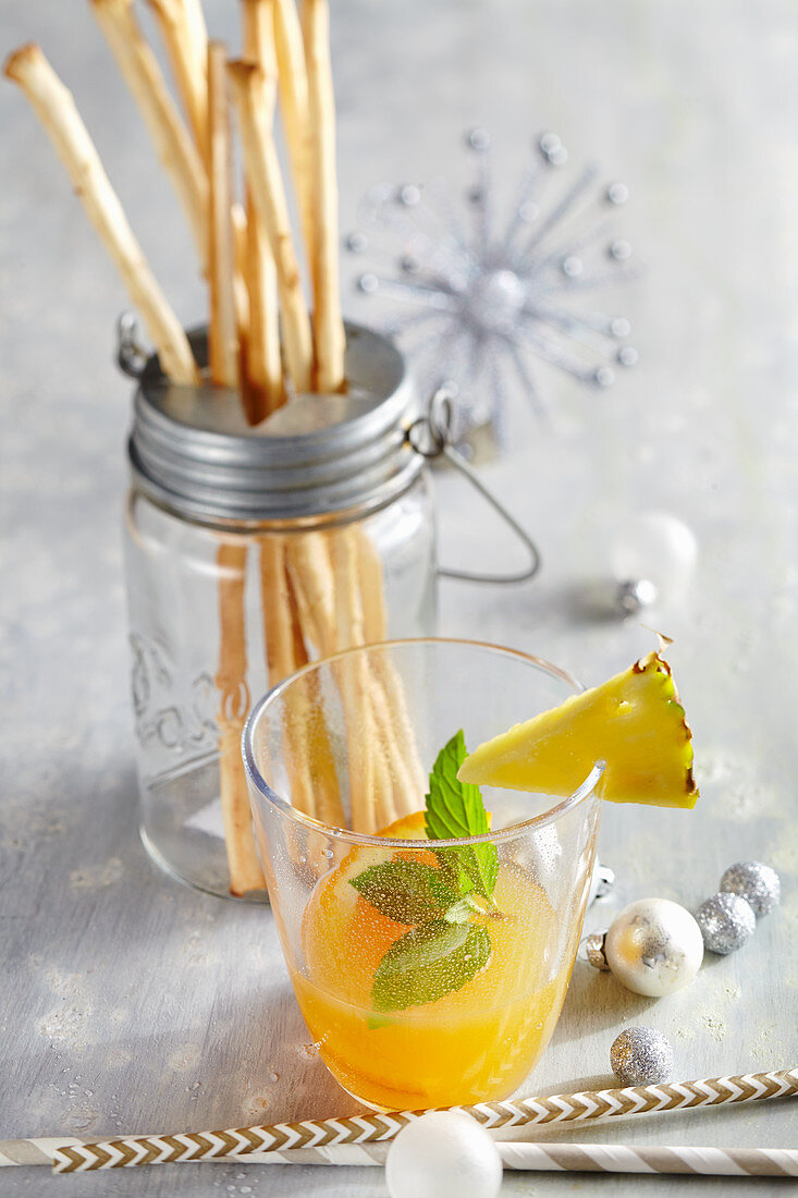 Christmas cocktail with winter apple liqueur, apple and orange juice with pineapple