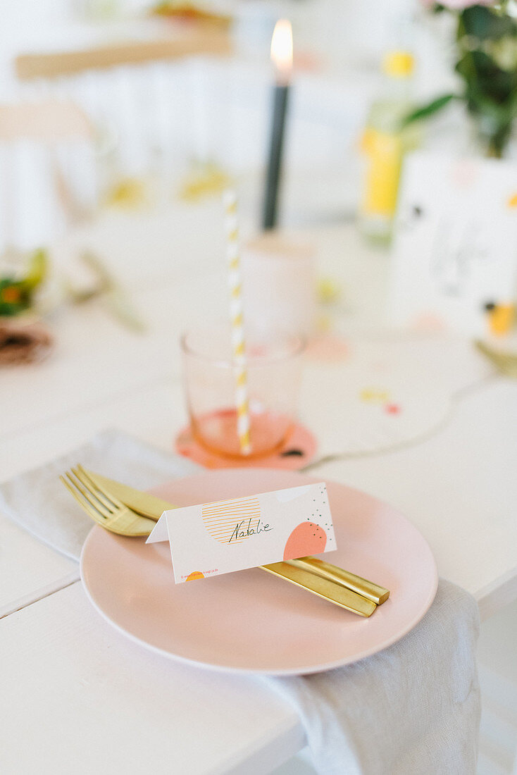 Table festively set with place cards and gold cutlery on pale pink plate