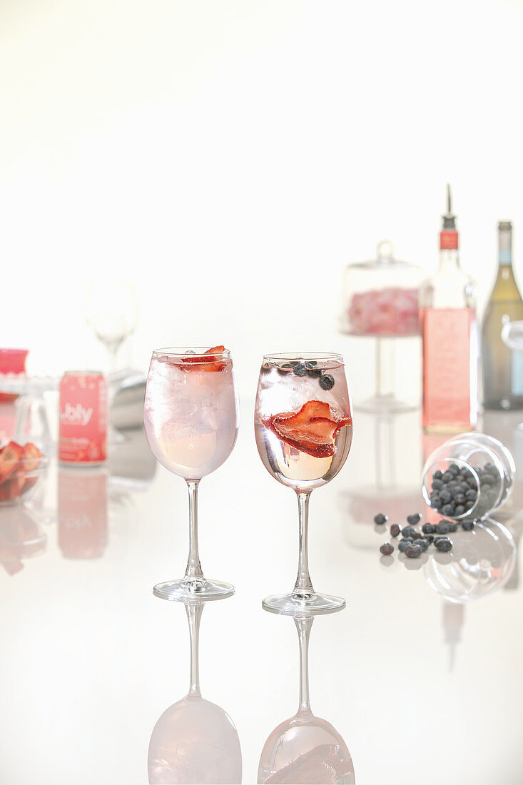 Pink gin cocktails in a variety of glassware