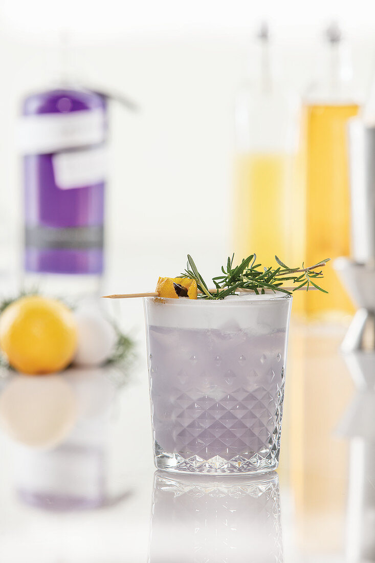 Purple gin cocktail with rosemary garnish