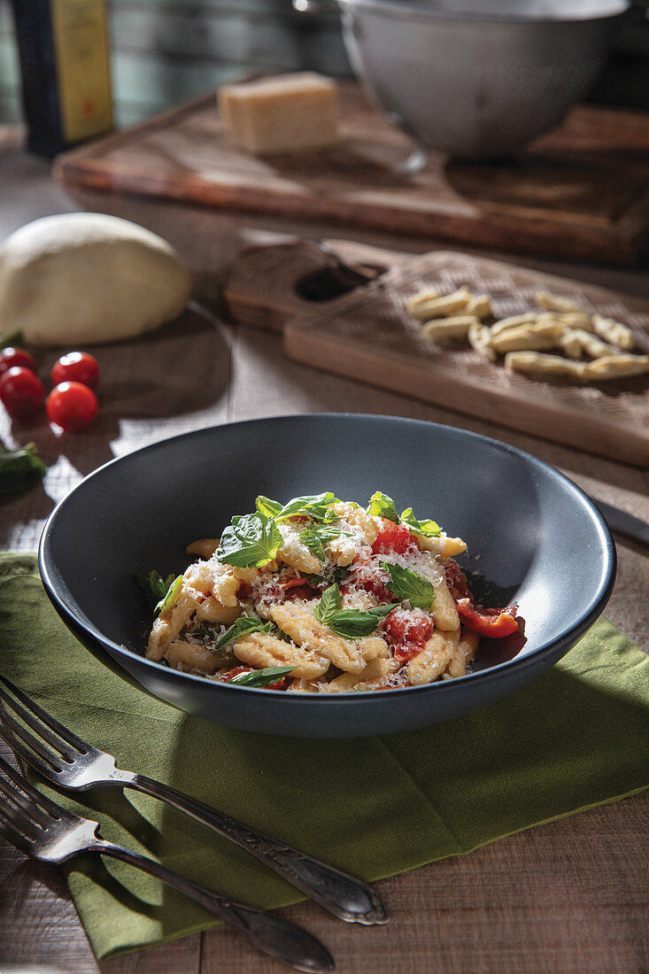 Home made pasta with cherry tomatoes and basil garnish in gray-blue bowl