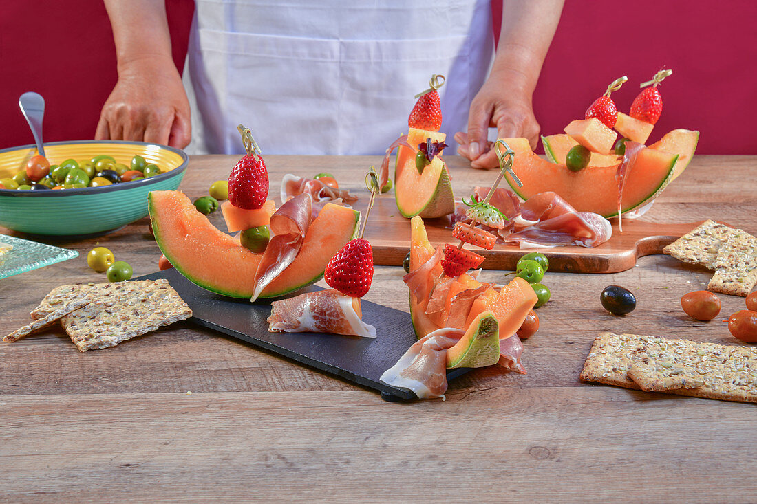 Faceless chef at table creating exquisite snack with fresh melon and ham on skewers with olives and berries