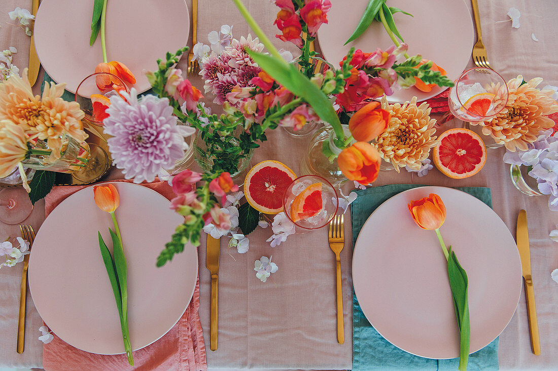 Table laid with flowers and pink grapefruits for Mother's Day