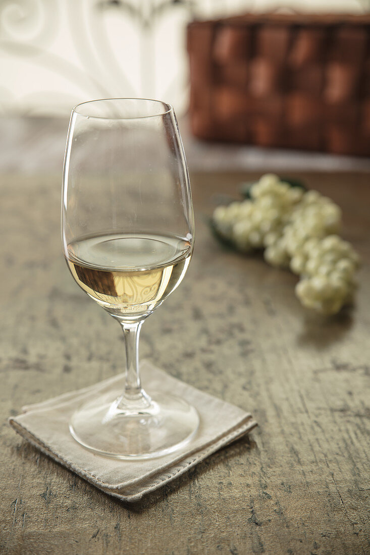 White wine with small white grapes in background