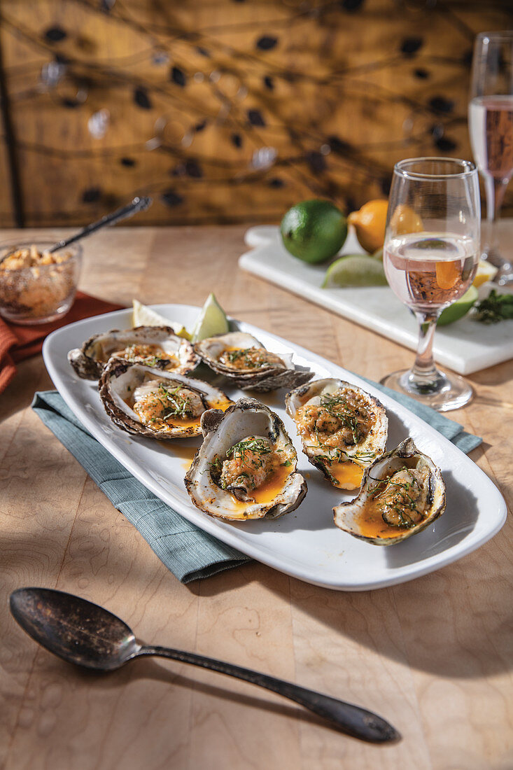 Smoked and Grilled Oysters on oblong with serving plate with rose in wine glass pairing