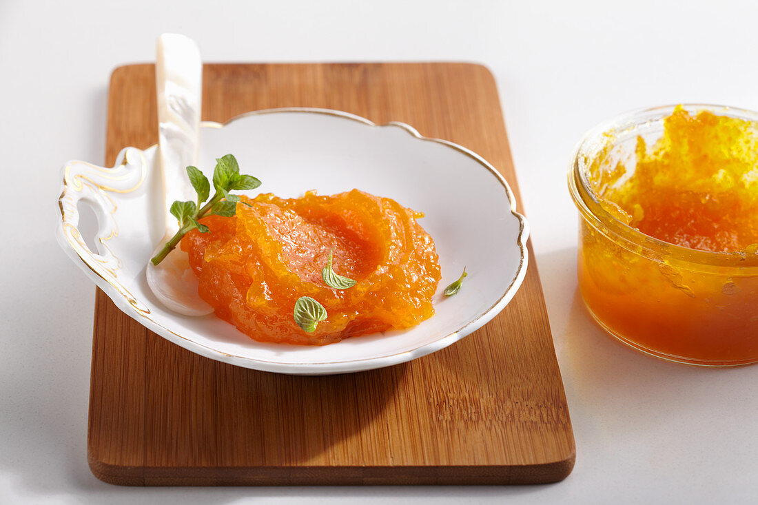Apricot and pumpkin preserve on an antique plate with a mother-of-pearl spoon