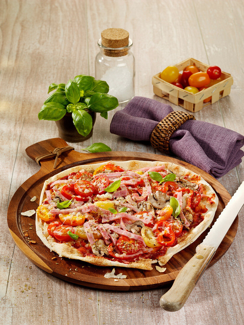 Bread pizza with ham, cherry tomatoes and peppers