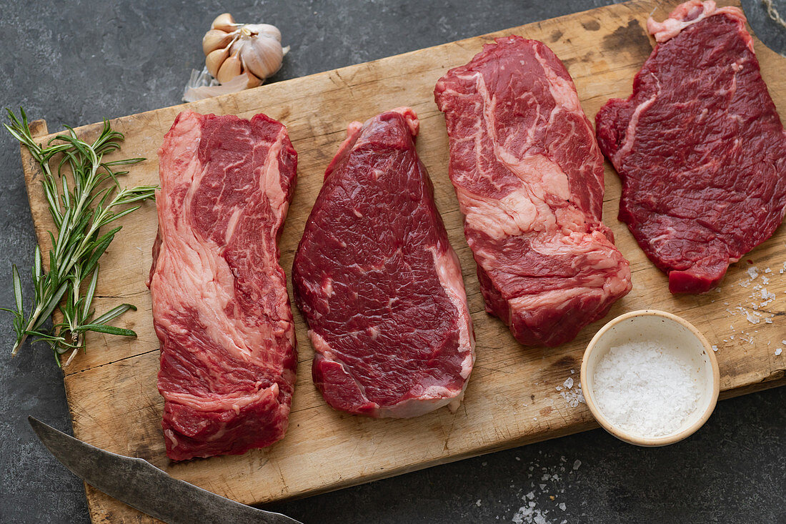 Various raw Black Angus steaks on a wooden board