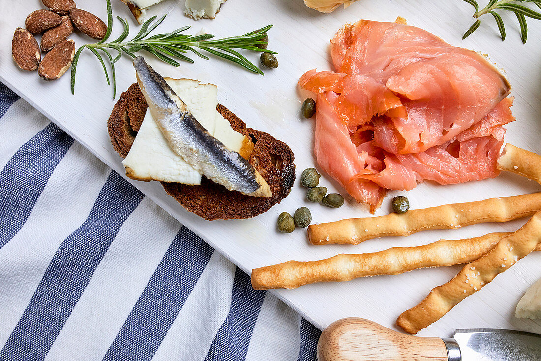 A Mediterranean appetizer platter with salmon, grilled bread and bread sticks