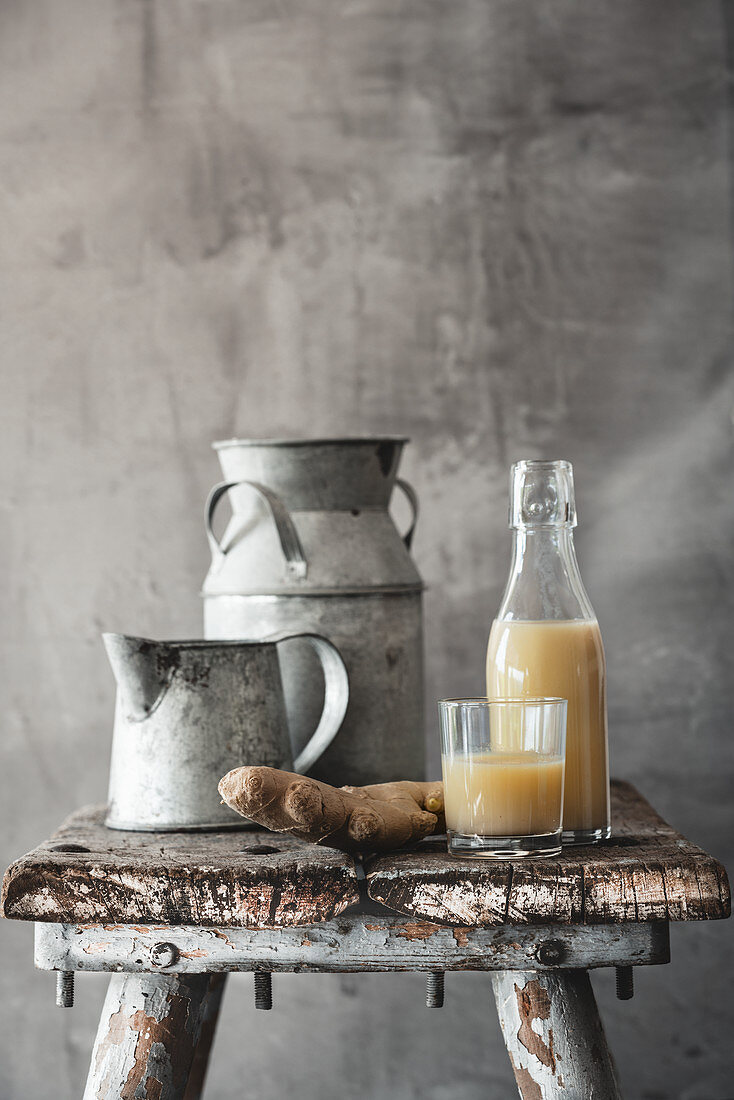 A ginger shot in a glass and a bottle on a rustic wooden stool