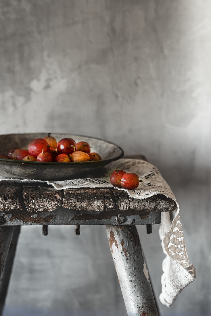 An arrangement of gooseberries in bowl on a rustic wooden stool