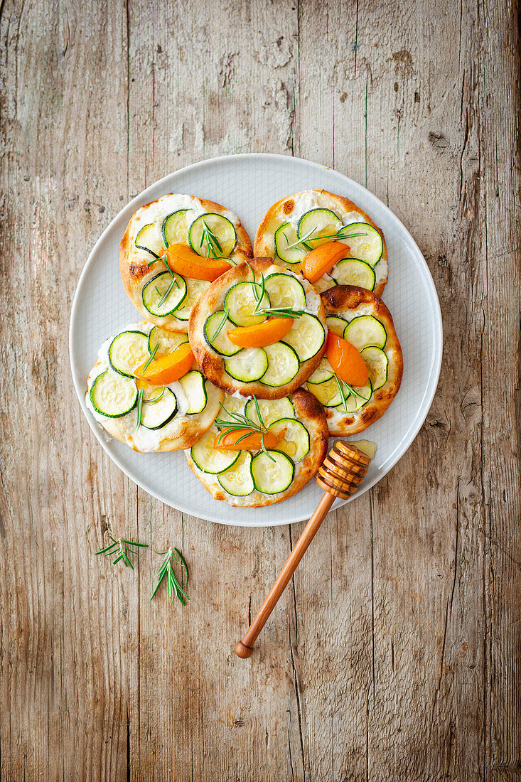 Small tarte flambées with goat's cream cheese, zucchini, apricots and honey on a tray