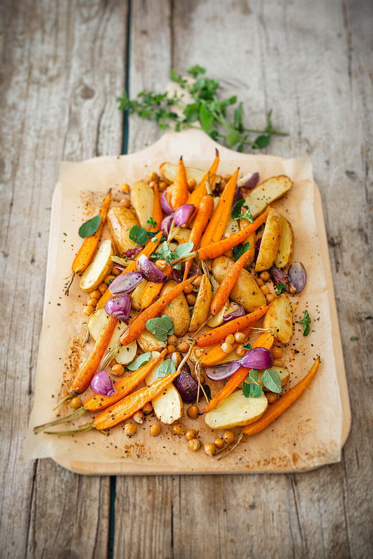 Potatoes, carrots and chickpeas with fresh oregano on a tray