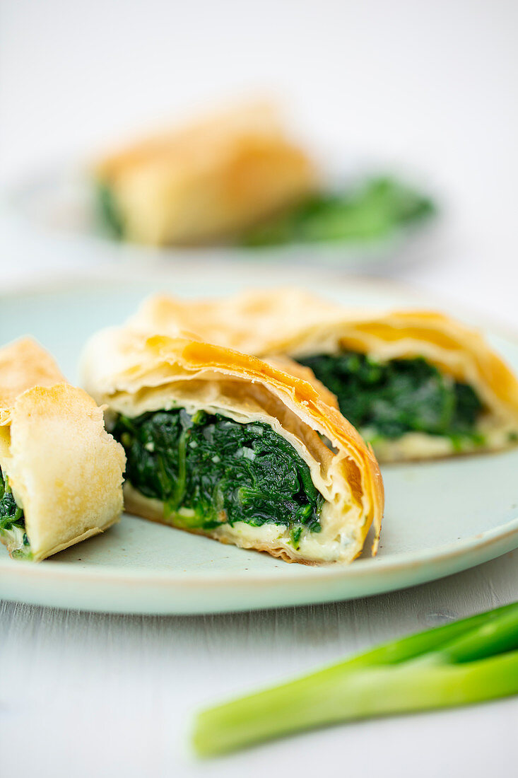Spinach strudel with spring onions and blue cheese from a tray
