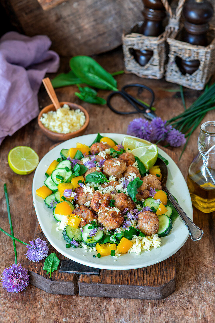 Meatballs and colourful vegetables on couscous