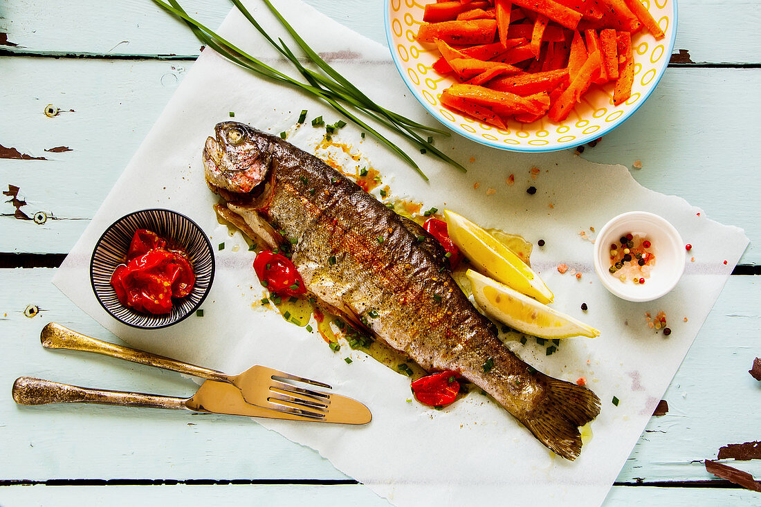 Baked Trout Fish and sweet potato on a turqouise surface