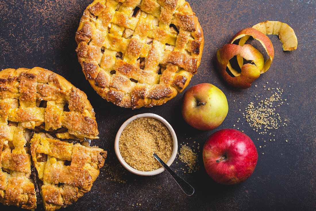 Top view of delicious homemade apple pie with cut slice, fresh apples, peel, cane sugar on brown rustic stone background