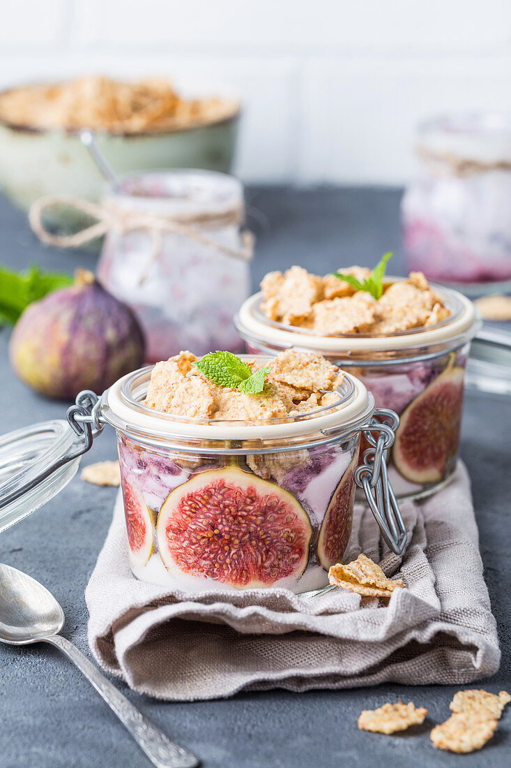 Homemade healthy yoghurt in glass pot with cereals, figs, mint on rustic concrete background