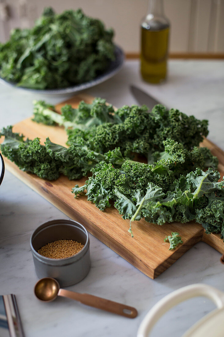 Kale on a kitchen board and mustard seeds in a tin can
