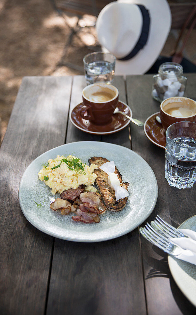 Scrambled eggs with bacon and toasted bread, with espresso on a table in the open air