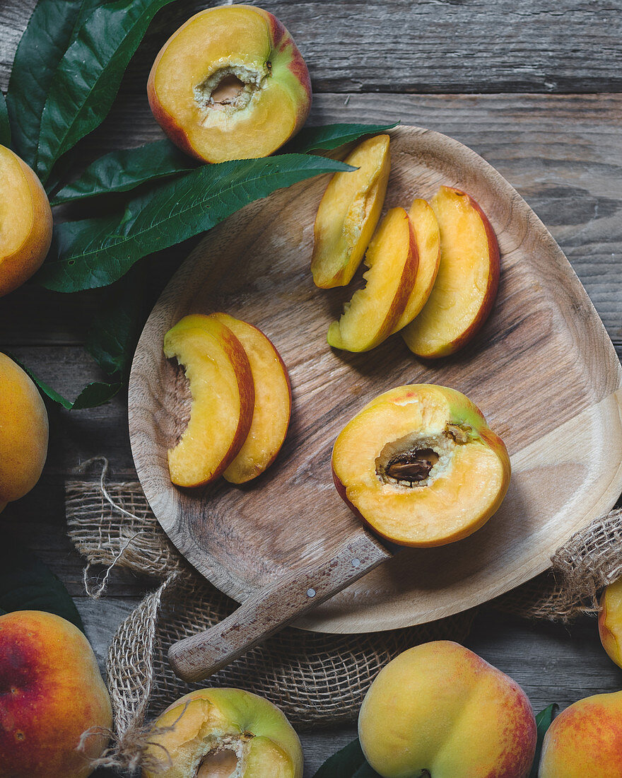 Wooden plate with peaches. peaches with leaves, wooden knife cutting peaches