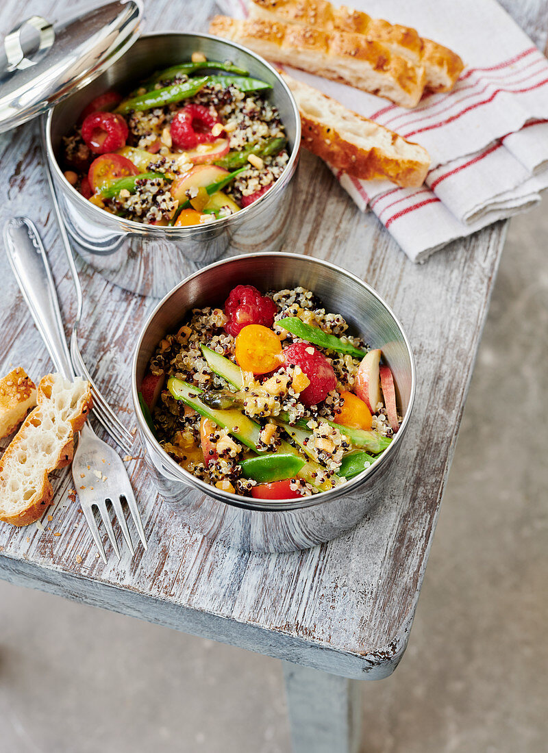 Fruity quinoa salad with chia, vegetables and cashews in to-go containers