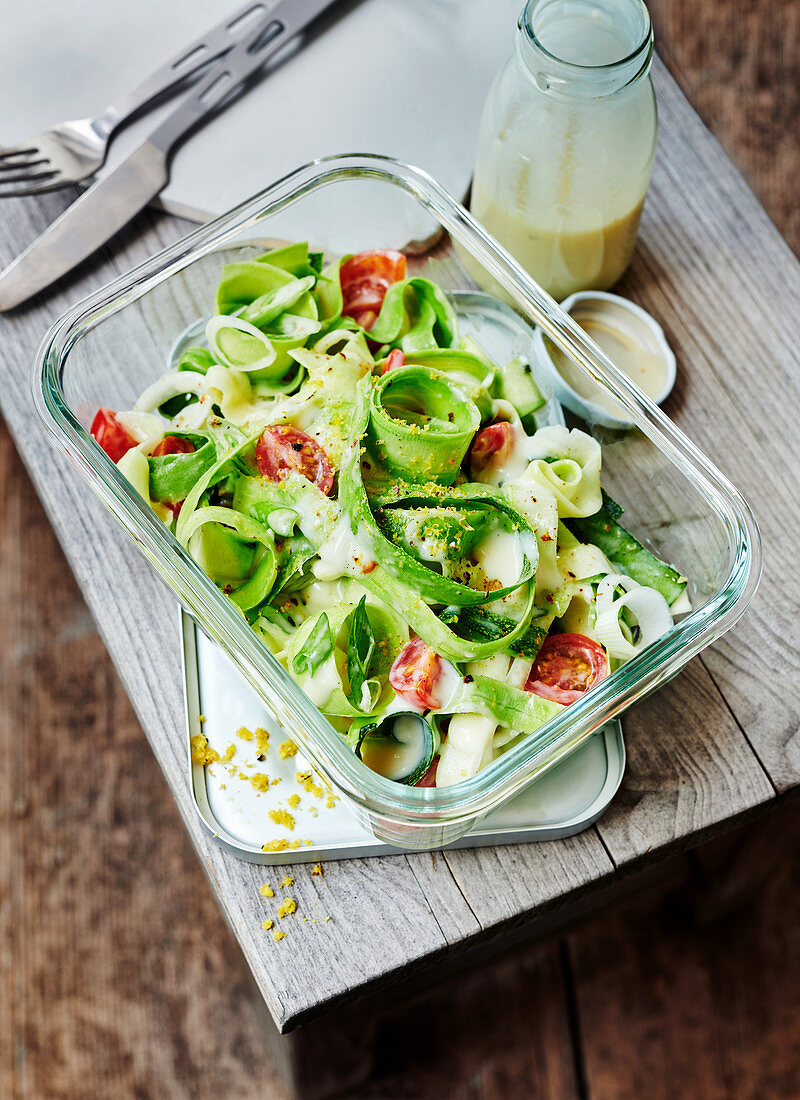 Zoodles with cherry tomatoes, spring onions and yoghurt mustard sauce in a to-go box